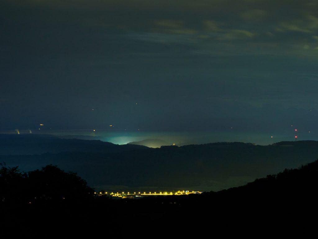 Nachtaufnahme von Dorflichtern hinter einer Bergkette