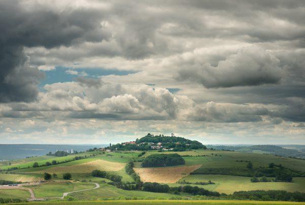 Kurzreisen vom Feinsten: Aussicht von einem Aussichtspunkt in Frankreich auf die umliegende Landschaft und das Dorf auf dem Nachbarhügel.